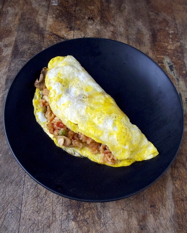Omurice Recipe - Who knew fried ketchup rice covered with an omelet could taste so good! This easy omurice recipe takes less than 20 minutes to make and serves 2. Recipe, omelet, Japanese, fried rice | pickledplum.com
