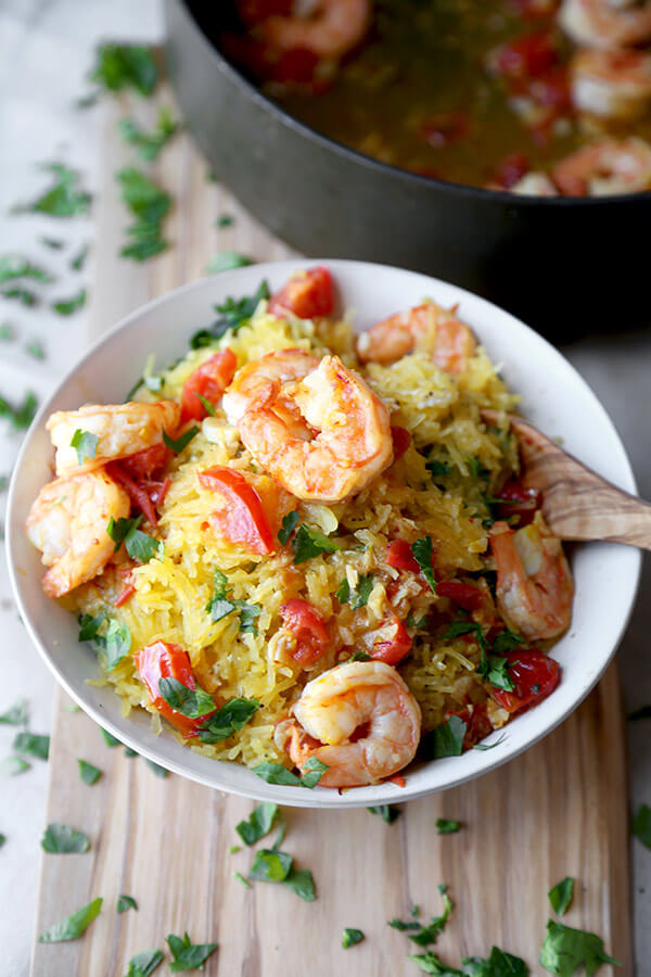 Shrimp scampi spaghetti squash - salty, lemony, buttery shrimp over a healthy bowl of spaghetti squash tossed in savory parmesan cheese. Totally yummy and ready in just 25 minutes! | pickledplum.com