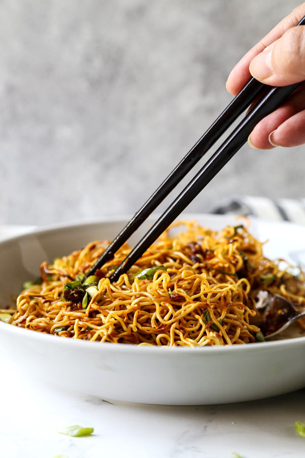 Pan Fried Noodles With Tangy Chili Crisp Sauce - Blanketed with herbs and plenty of smokey, pungent, fragrant heat, this pan fried noodles recipe is ready in under 20 minutes from start to finish! #eggnoodles #chineserecipes #noodlerecipe #stirfry #veganrecipes | pickledplum.com